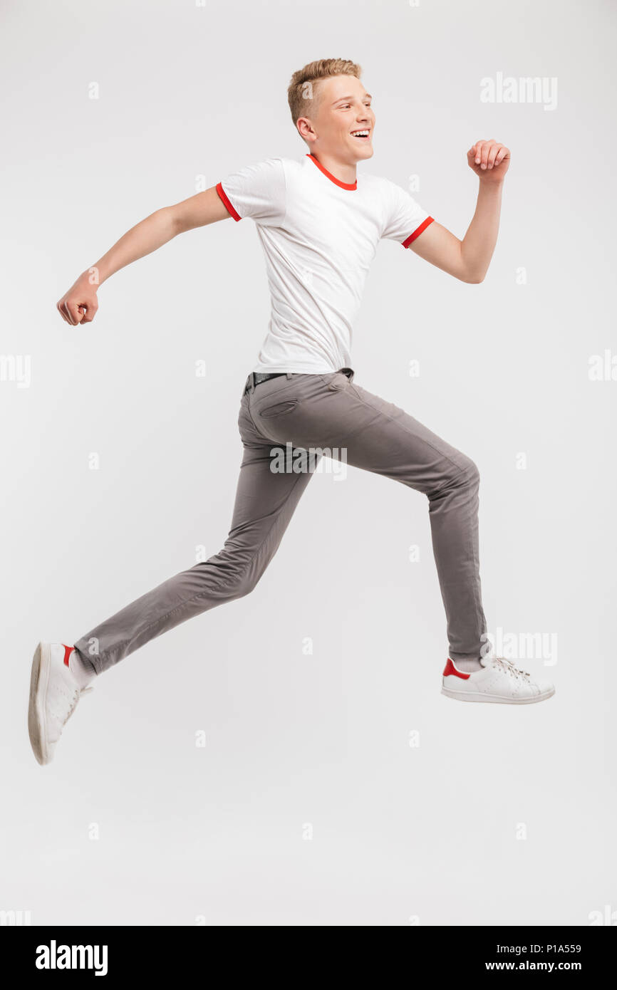 Full length portrait of happy caucasian teenage boy 16-18 years old in streetwear smiling while running isolated over white background - Stock Image