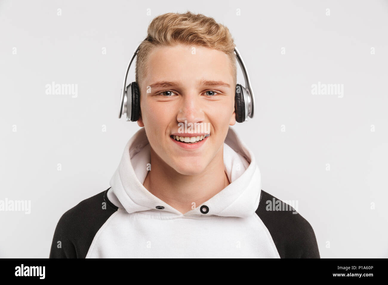 Portrait closeup of teenage boy 16-18 years old wearing hoodie and wireless headphones posing with happy smile isolated over white background - Stock Image
