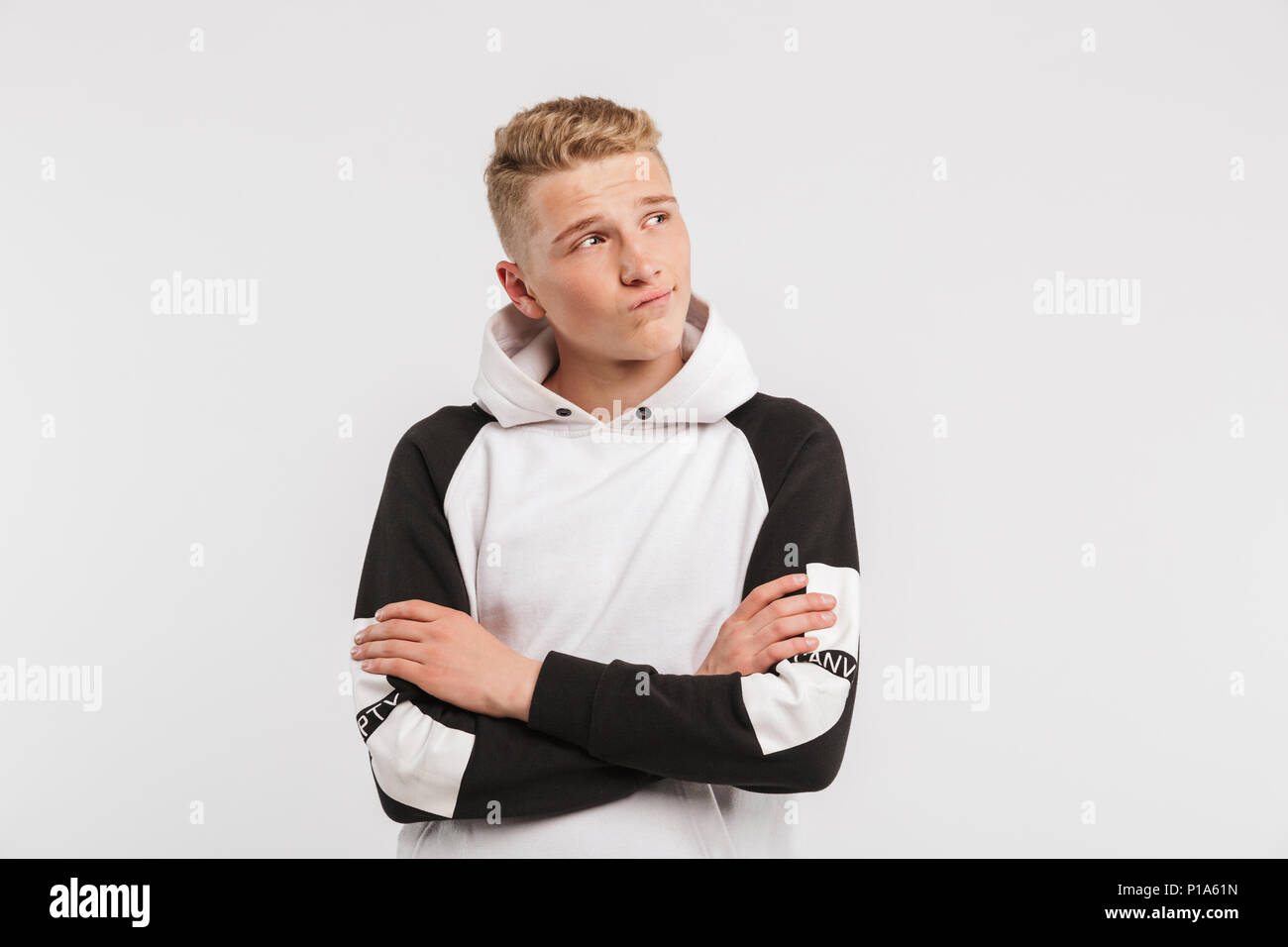 Portrait closeup of teenage boy 16-18 years old wearing hoodie looking aside at copyspace with arms crossed isolated over white background - Stock Image
