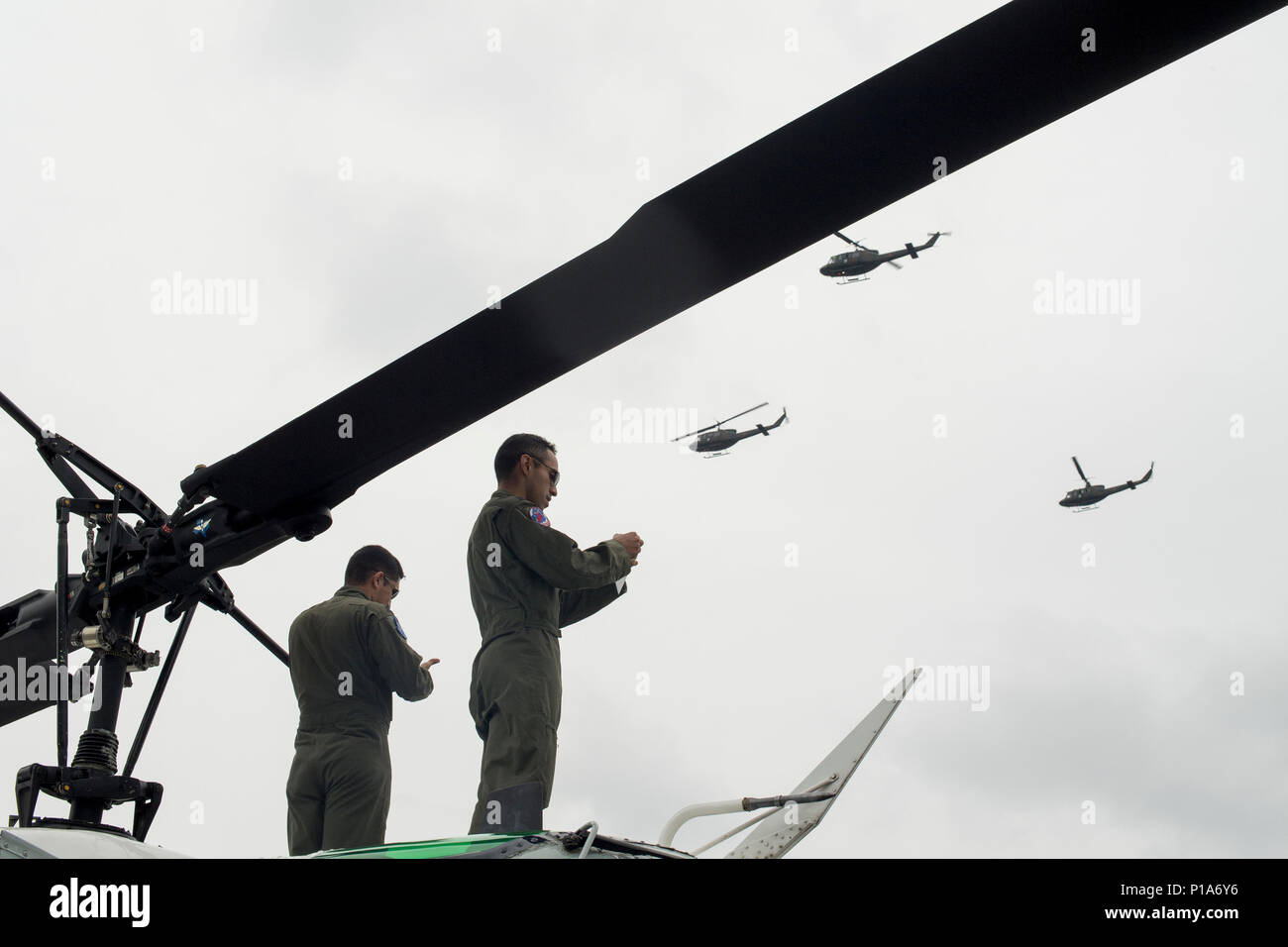 (Right to left) U.S. Air Force Capt. Jonathan Bonilla and Capt. Vicente Vasquez, 459th Airlift Squadron UH-1N Iroquois pilots, take photos of a Japan Ground Self-Defense Force UH-1J Huey formation flight display during the 43rd Anniversary Event of Japan Ground Self-Defense Force Camp Tachikawa at JGSDF Camp Tachikawa, Japan, Oct. 1, 2016.  JGSDF UH-1Js assigned to Eastern Army Helicopter demonstrated flight formations, hoist techniques and disaster relief procedures with first responders. Service members with the 459th Airlift Squadron from Yokota Air Base and Army Aviation Battalion from Cam Stock Photo