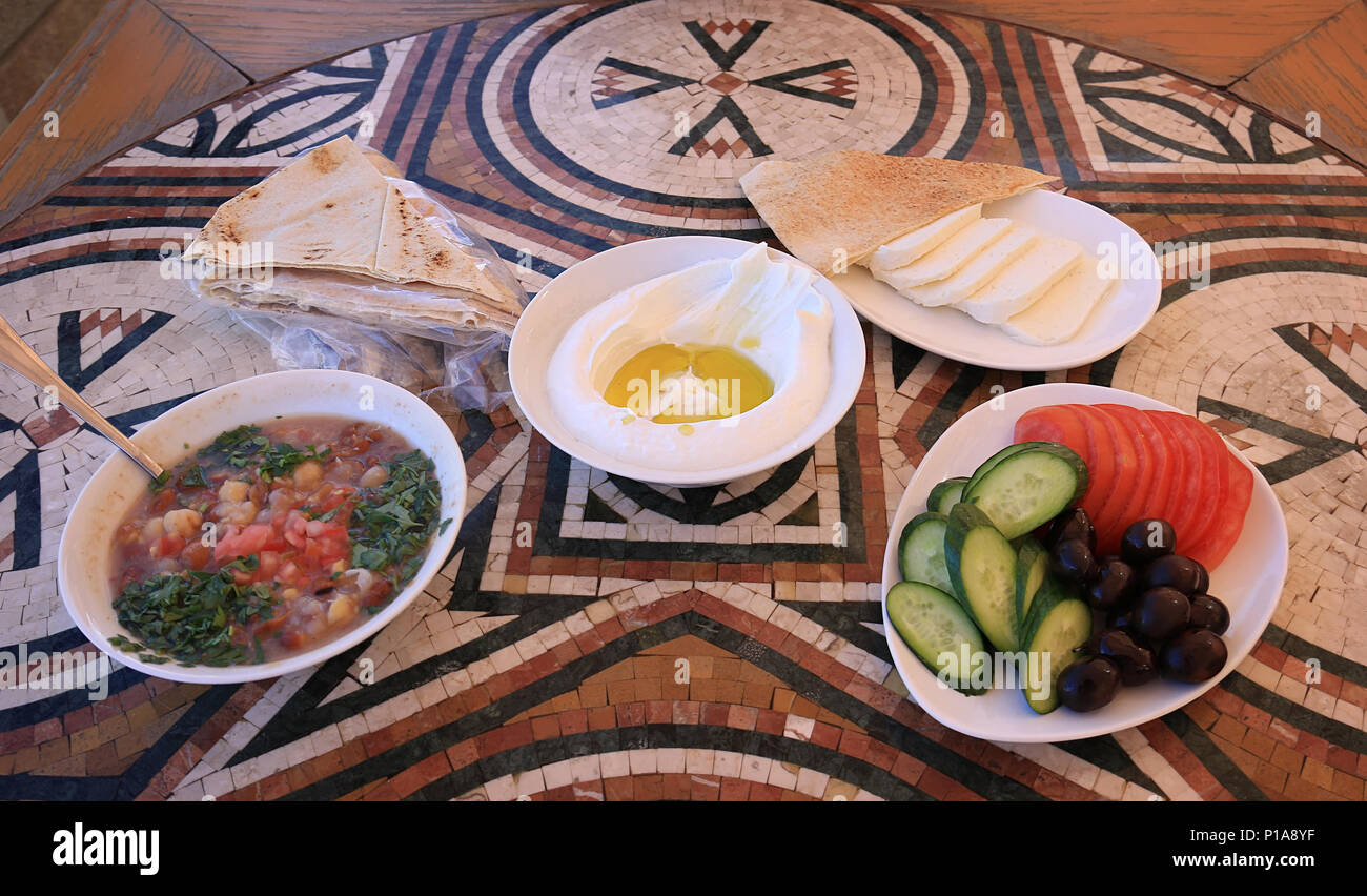 A Lebanese breakfast setup on a mosaic table. The various dishes are labneh, foul mdammas, halloumi cheese slices, and olives, cucumbers, and tomatoes - Stock Image