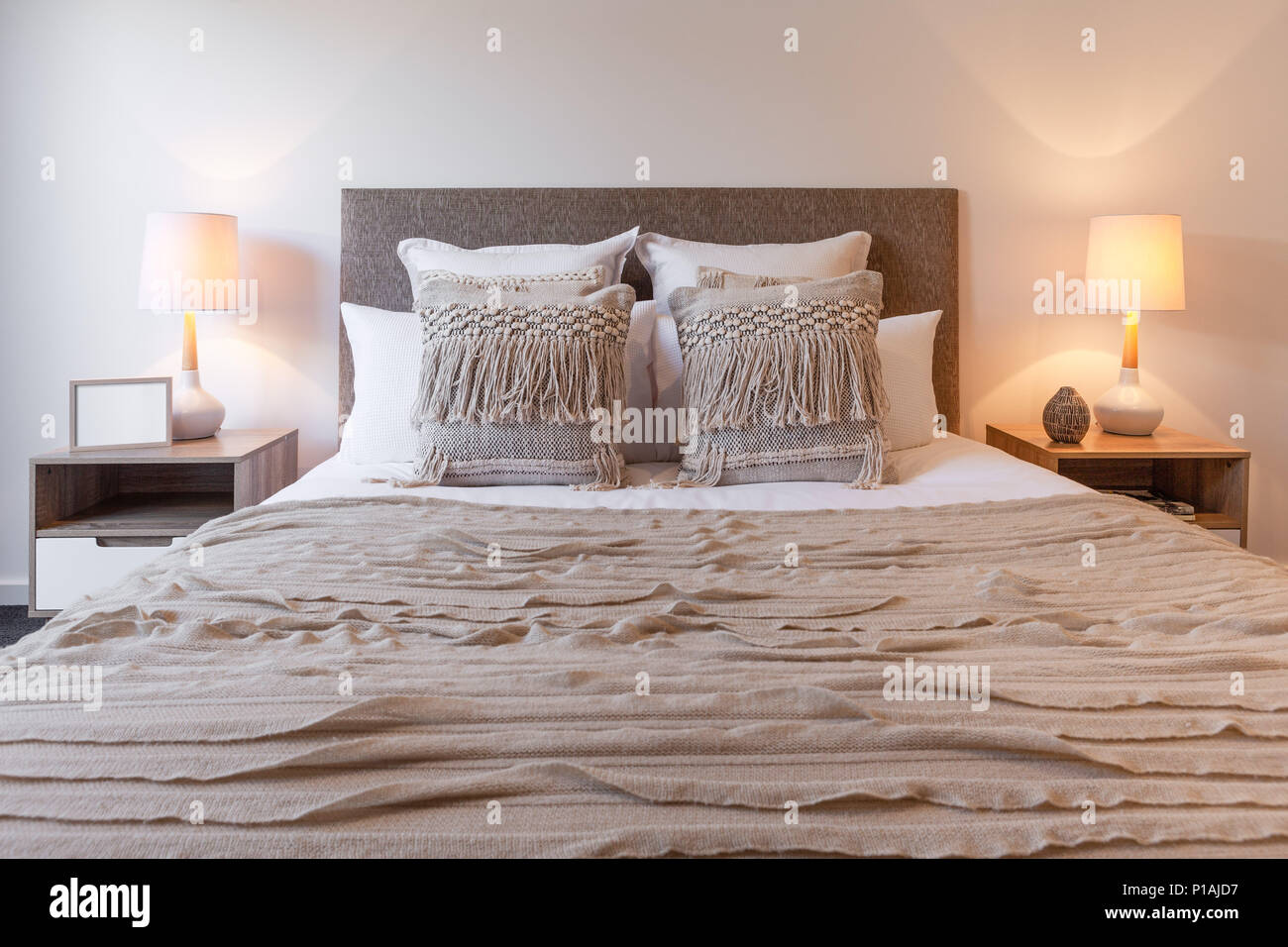 Decorative Pillows On Bed Arrangement With Bedroom Lamps And Bedside Tables