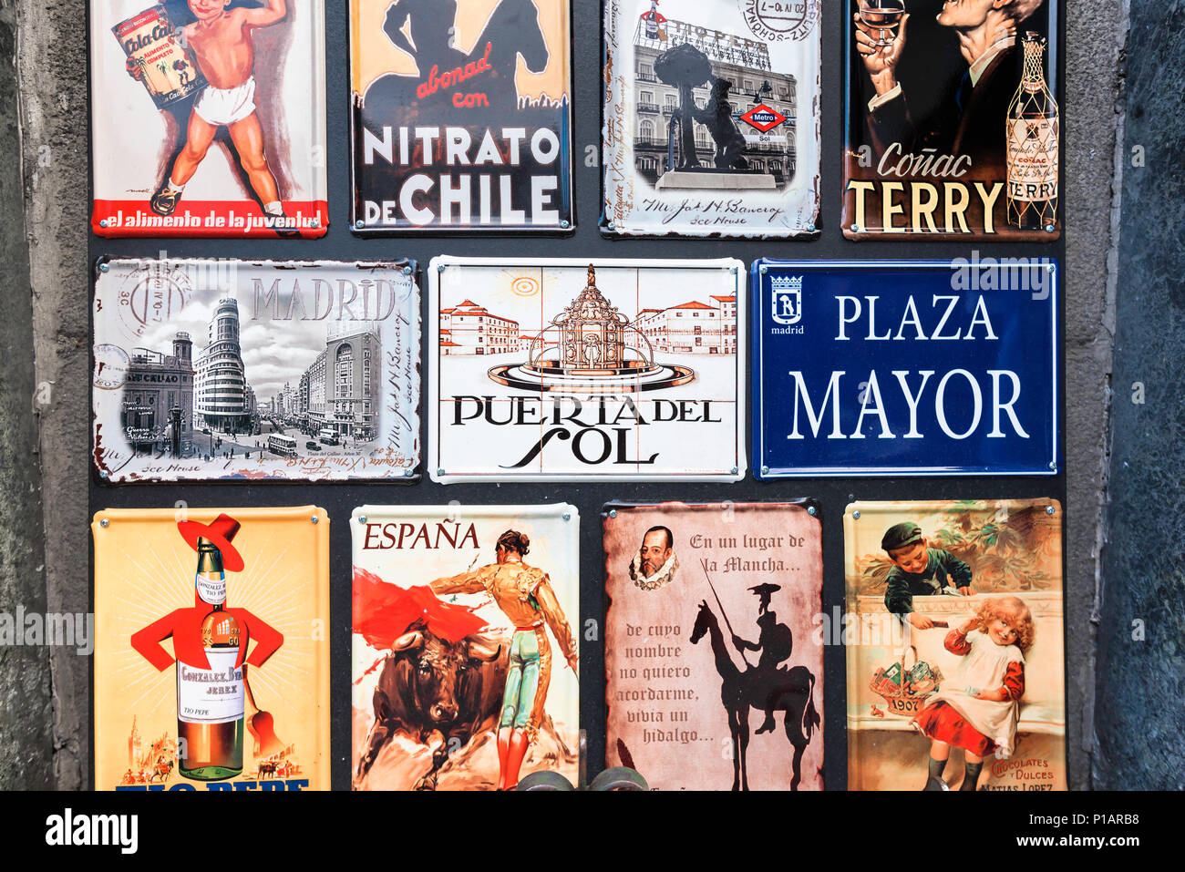 A collection of souvenir plaques for sale to tourists in the Puerta del Sol showing the attractions of Madrid or Spain. - Stock Image