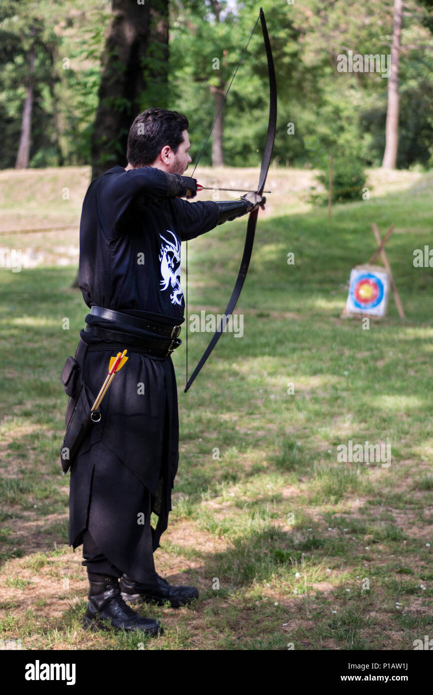 Nis, Serbia - June 10, 2018: Medieval archer with big wooden bow and long arrow in forest. Living history festival. Archery tournament Stock Photo