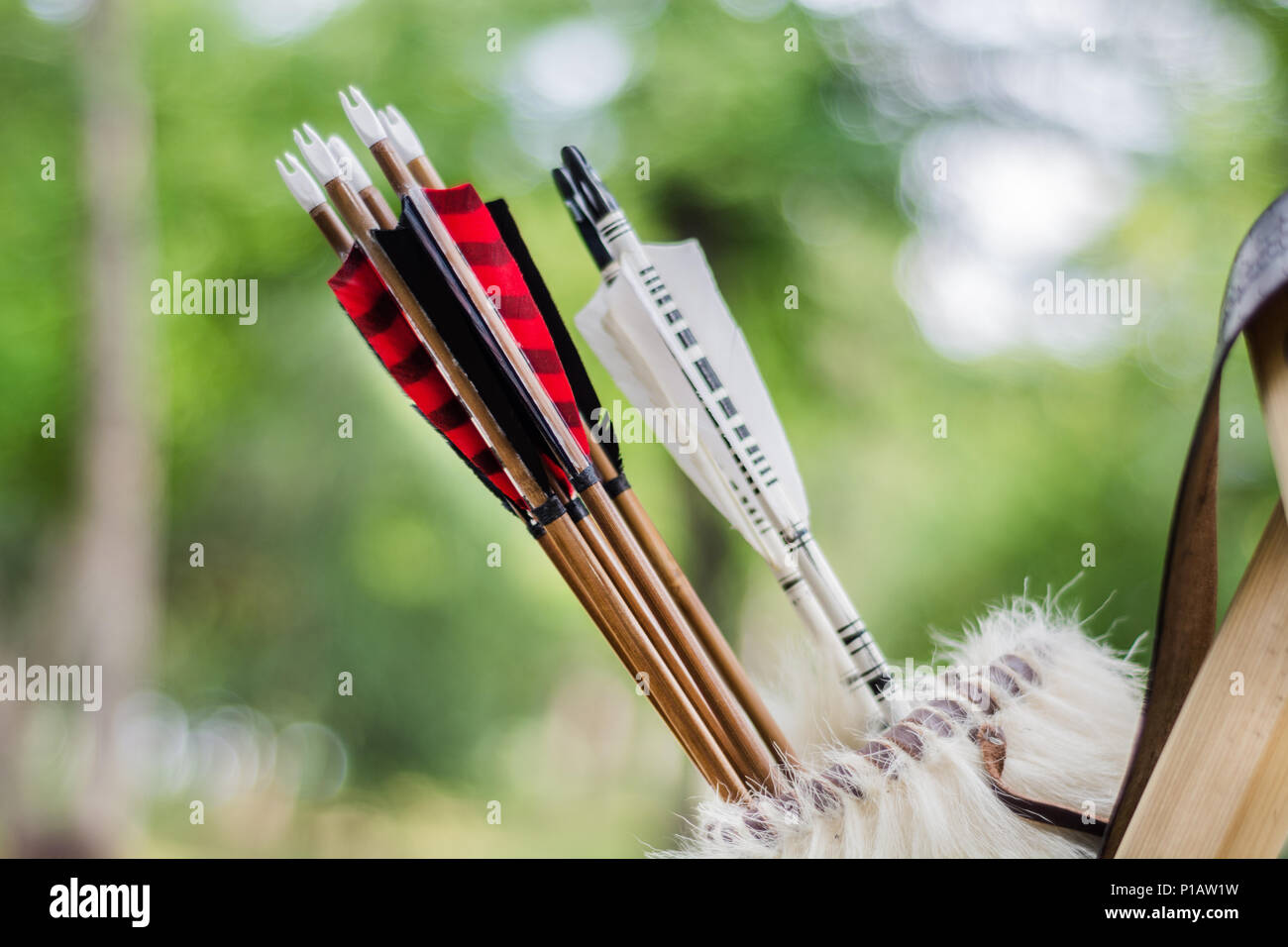 Medieval set of old colorful wooden arrows hanging on stand in bag. Close up, selective focus - Stock Image