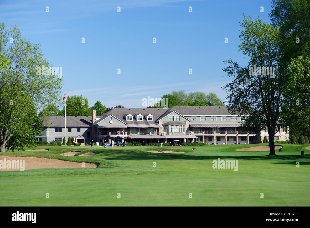 View of a green and of the expansive clubhouse of the exclusive Royal Montreal Golf Club, Ïle Bizard, province of Quebec, Canada. - Stock Image