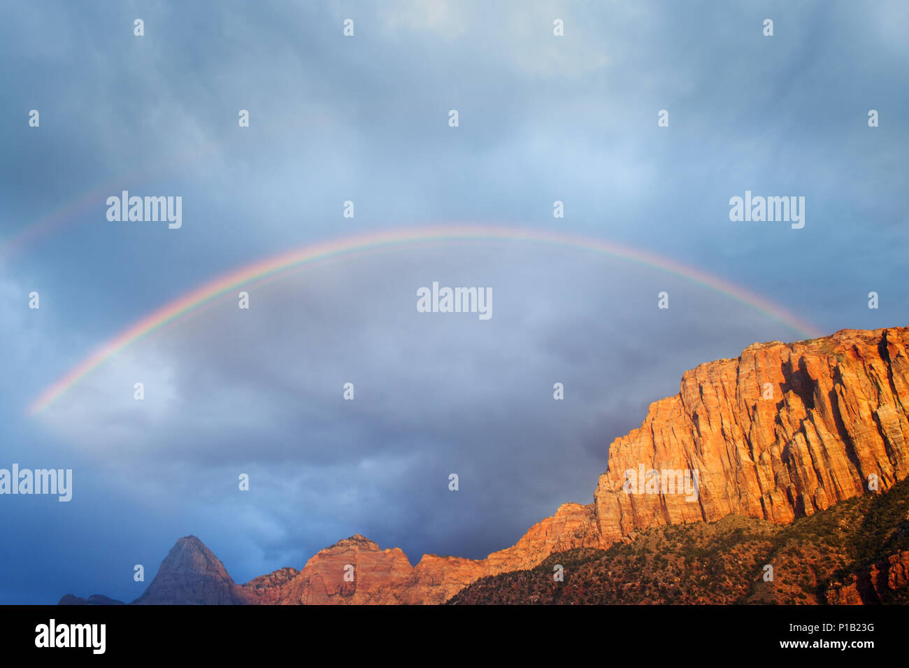 Partial double rainbow over a red rock cliff near Zion National Park, Utah, USA. - Stock Image