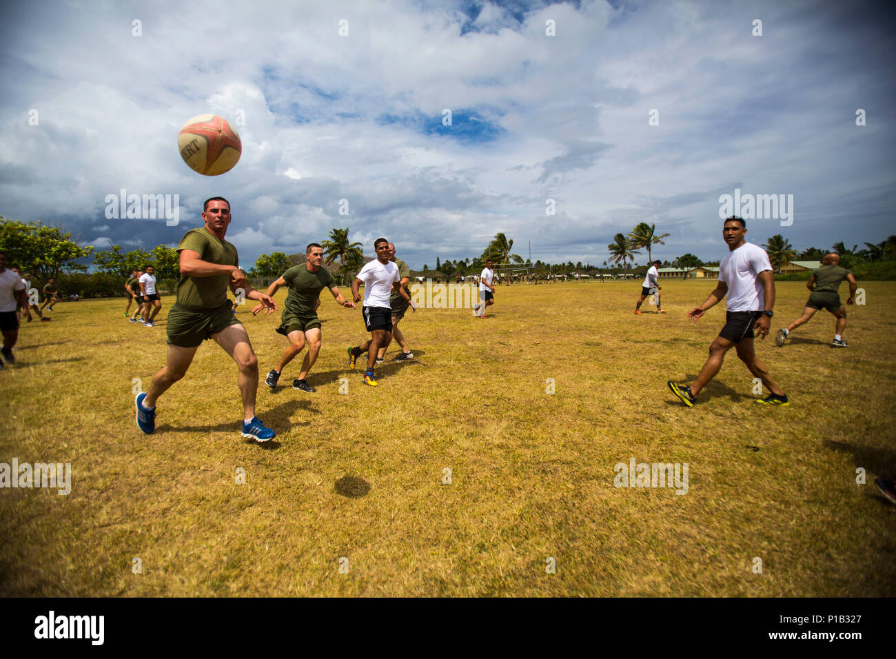 TALIAI, Tonga – U.S. Marine Lance Cpl. Nicholas Maclaren, left, a combat engineer with Combat Engineer Platoon, Task Force Koa Moana 16-4, passes a ball during a rugby game in Taliai, Tonga, Oct. 8, 2016. During Exercise Koa Moana, U.S. service members and His Majesty's Armed Forces worked together to enhance and improve military-to-military relations. (U.S. Marine Corps Photo by Cpl. James Treviño) - Stock Image