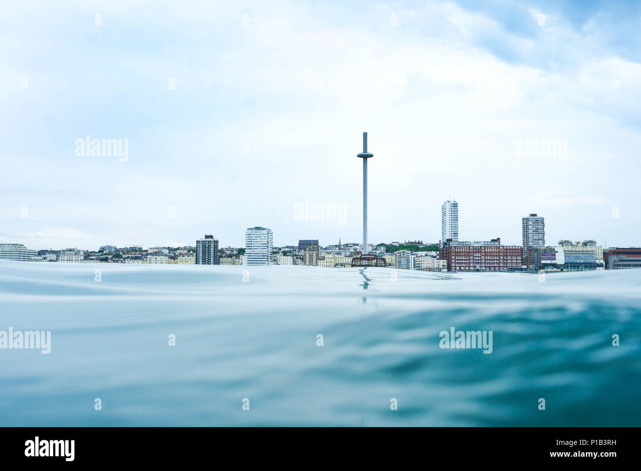 Brighton seafront view point from the sea, at the bottom is a calm glass like flat sea in the middle is the skyline of Brighton, UK, with the I360 vie - Stock Image