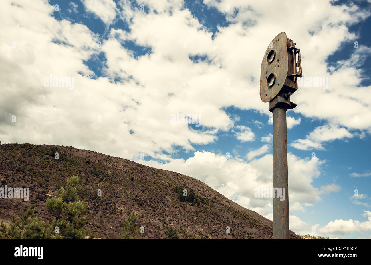 Old rusty train semaphore with sky and mountain background in the old station of Zaranda, Spain - Stock Image