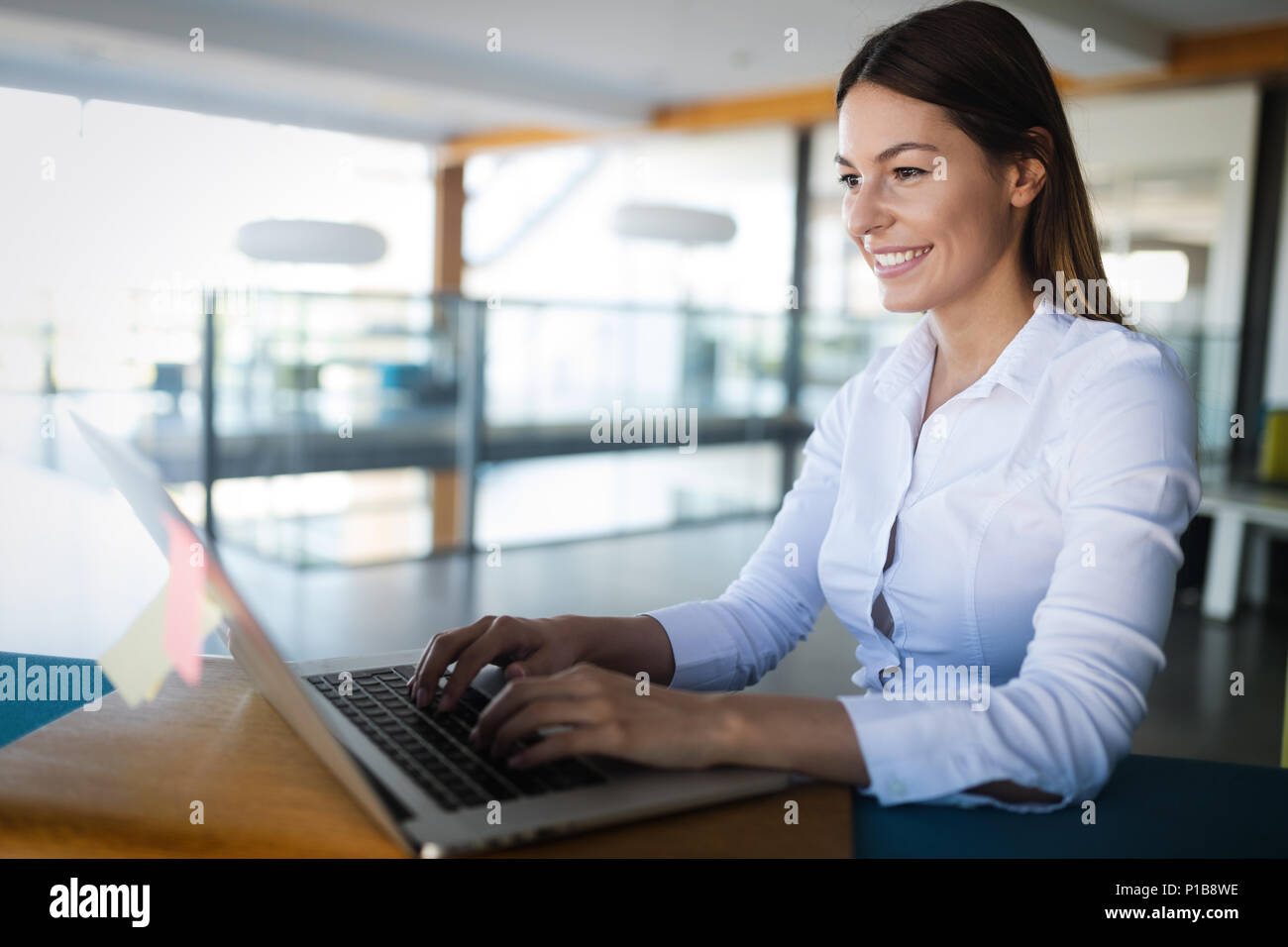 Attractive young female architect working on laptop - Stock Image