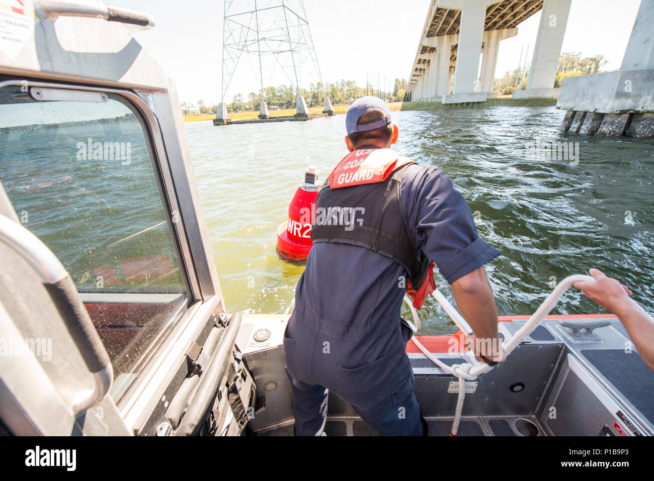 Seaman Elijah Squartsoff connects a towline to a buoy Oct. 10, 2016 in Skull Creek, South Carolina. Coast Guard crews worked diligently to verify and repair aids-to-navigation to reopen the Port of Savannah following Hurricane Matthew. U.S. U.S. Coast Guard photo by Petty Officer 2nd Class Christopher M. Yaw/PADET Jacksonville D7 External Affairs Stock Photo