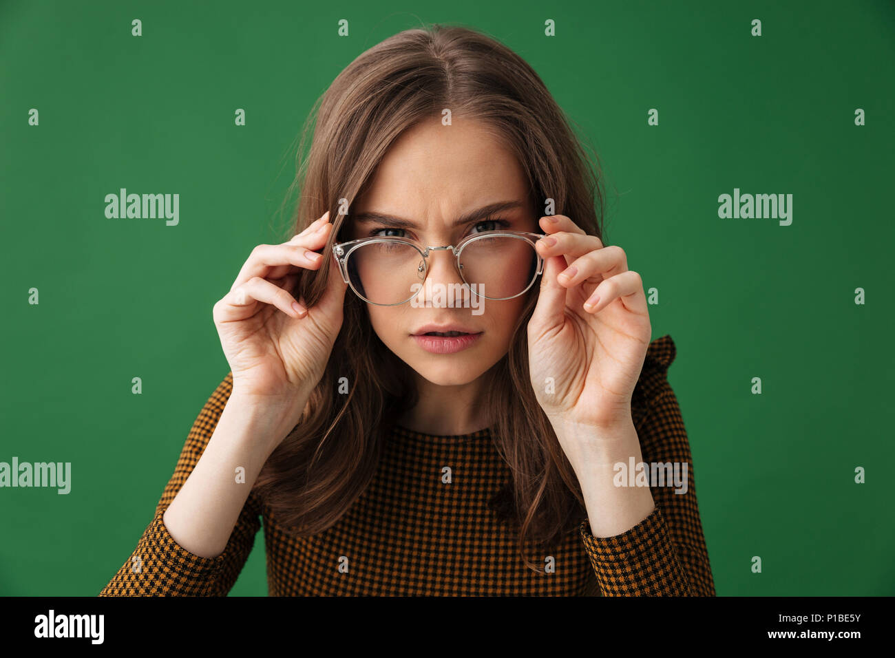 a27081bebd9 Image of young serious woman standing isolated over green background  wearing glasses looking camera. -