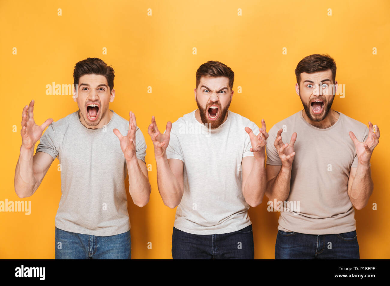 Three young angry men screaming isolated over yellow background - Stock Image