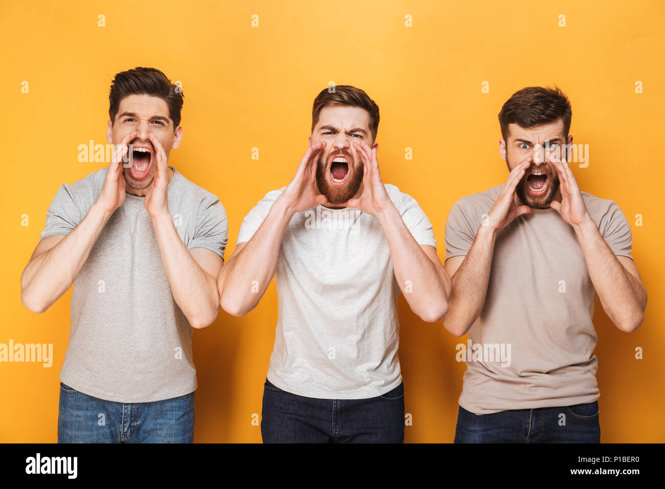 Three young angry men shouting isolated over yellow background - Stock Image