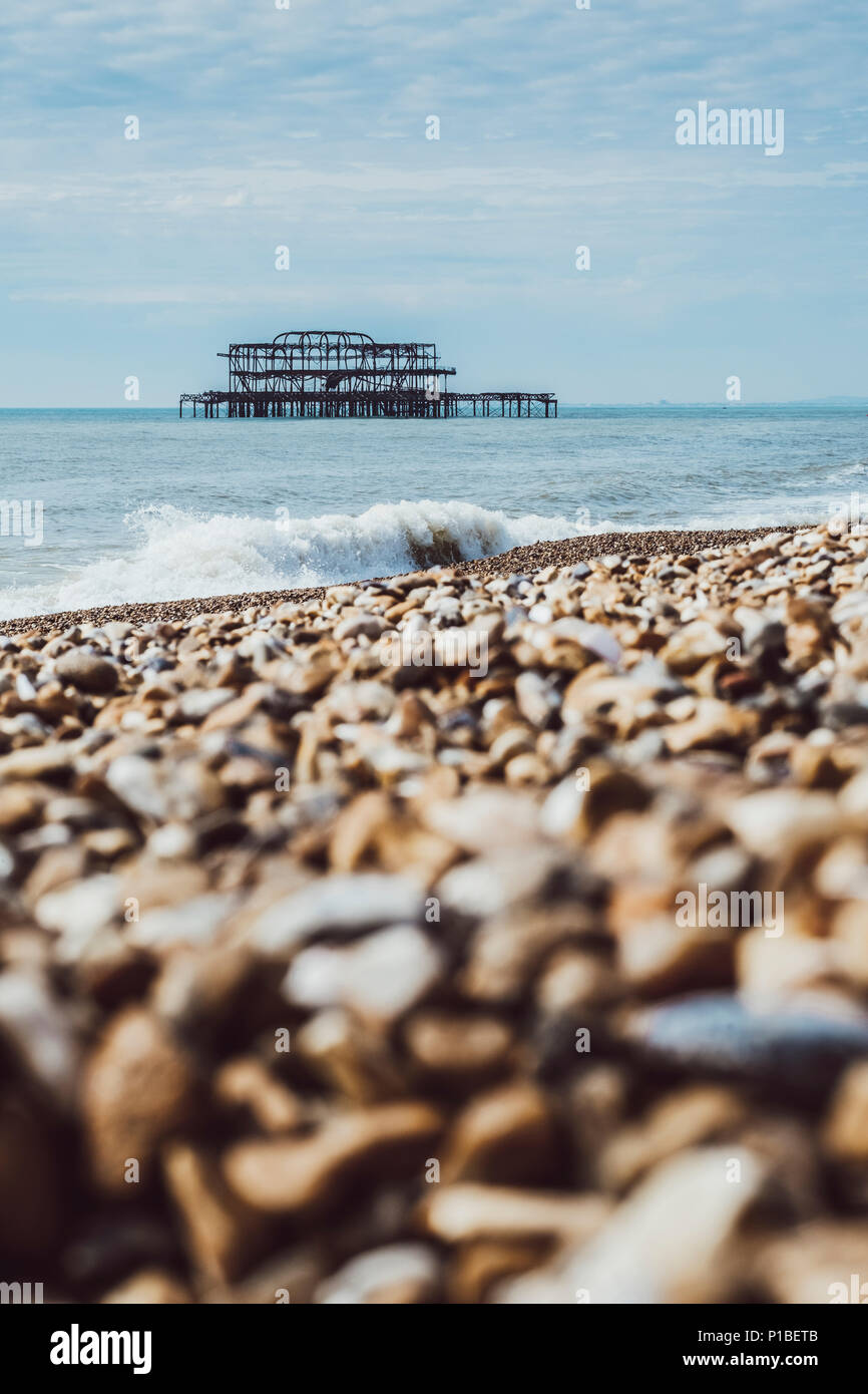 Burned West Pier by the sea, Brighton, England - Stock Image