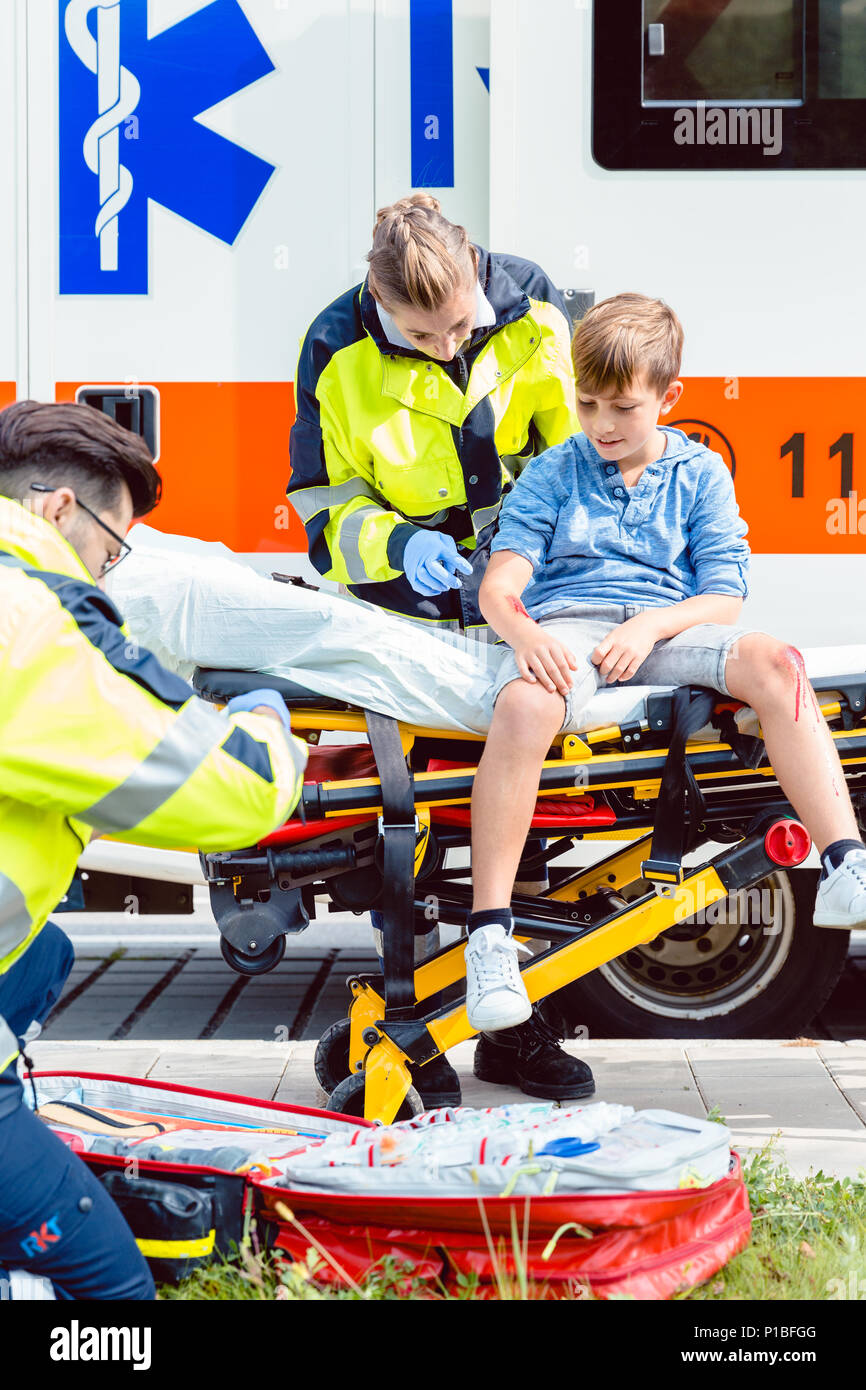 Emergency doctors caring for accident victim boy - Stock Image