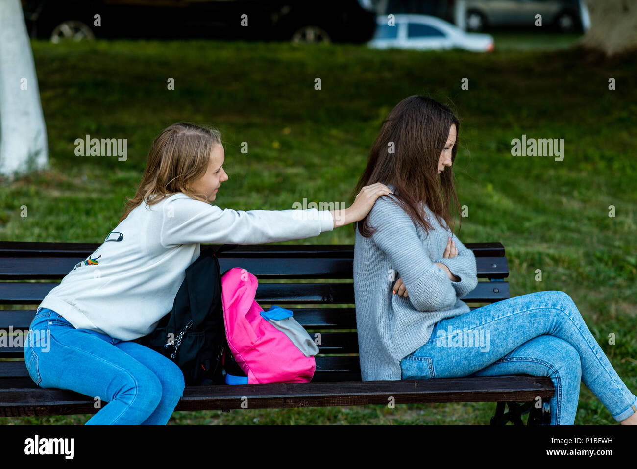 Two girlfriends in summer on the bench. Offended each other. Friends quarreled. Nigativa among girls. The problem is in the relationship. Dissatisfaction with each other. - Stock Image