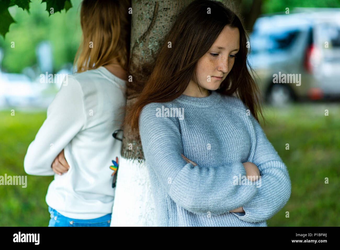Two girlfriends in the summer in a park in nature. Offended each other. Friends quarreled. Negative among the girls. Problems in the relationship. Dissatisfaction with each other. Stand near a tree. - Stock Image