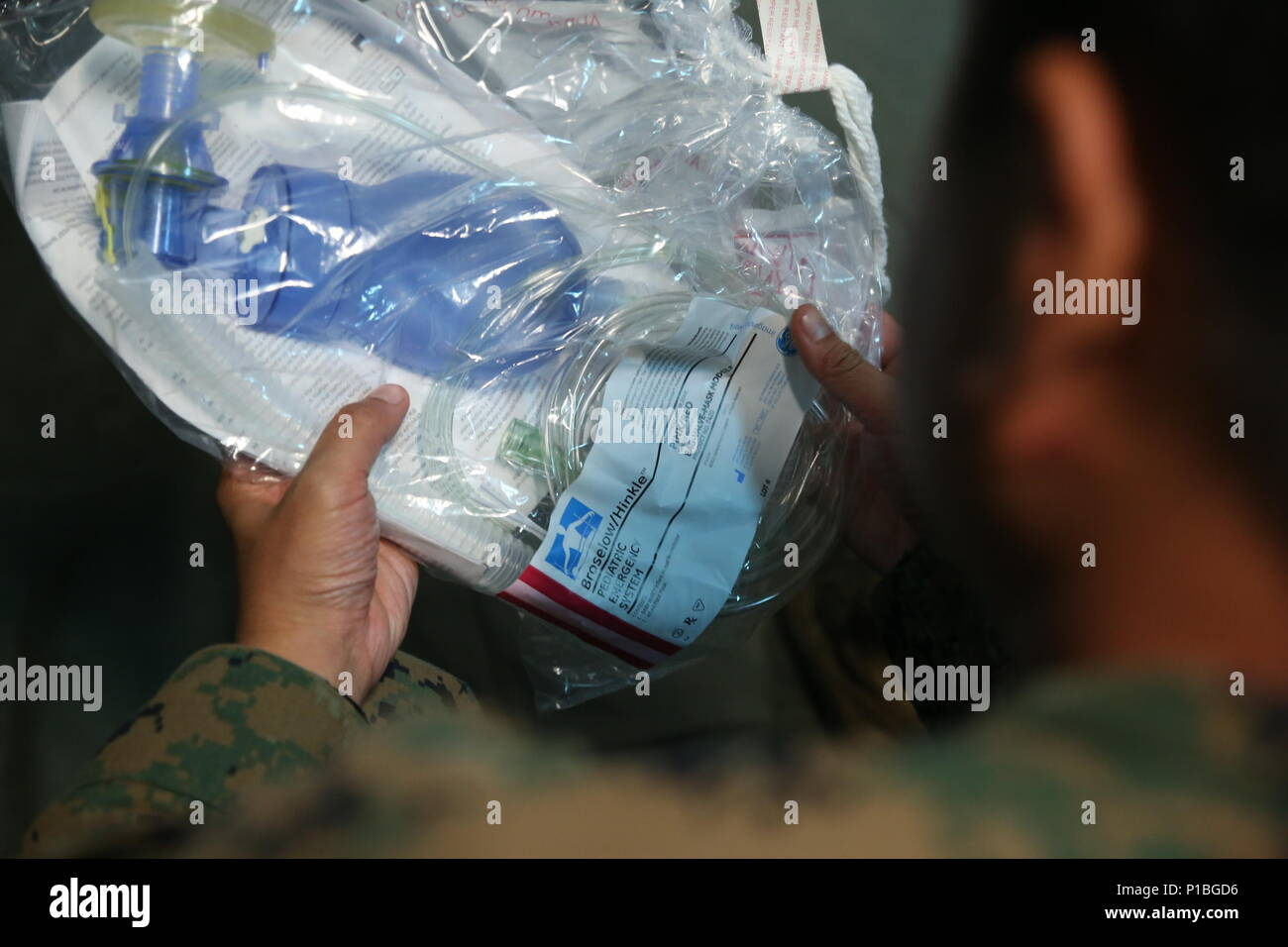A U.S. Sailor with Shock Trauma Platoon, Combat Logistics Battalion 31, 31st Marine Expeditionary Unit, inspects a pediatric bag valve mask, a medical instrument used in cases of pediatric respiratory failure, during pediatric malady training as part of Amphibious Landing Exercise 33 (PHIBLEX 33) at Col. Ernesto Ravina Air Base, Philippines, Oct. 8, 2016. Shock Trauma Plt. conducted the training during PHIBLEX 33 to prepare its Sailors to treat child patients. PHIBLEX 33 is an annual U.S.-Philippine military bilateral exercise that combines amphibious capabilities and live-fire training with h - Stock Image