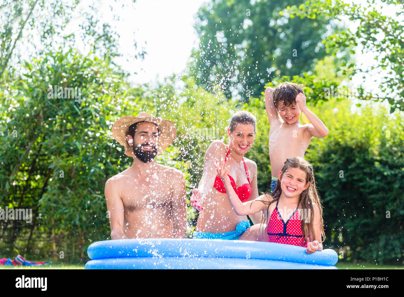 Family cooling down splashing water in garden pool  - Stock Image
