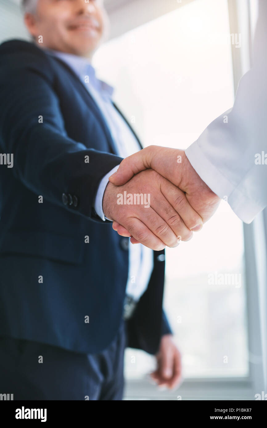 Alert businessman shaking hands with the doctor Stock Photo