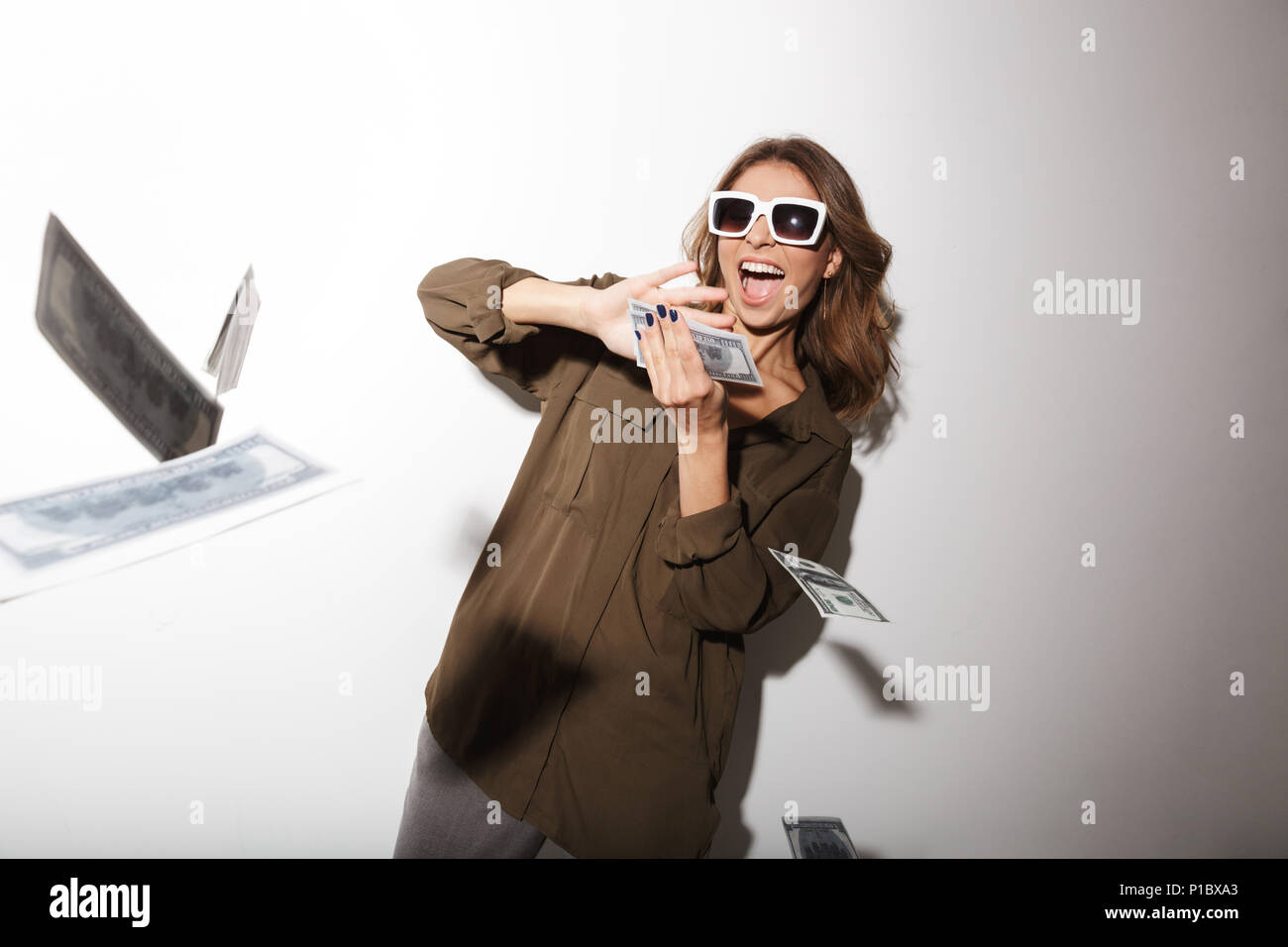 Portrait of a joyful young woman in sunglasses throwing out money banknotes isolated over white background - Stock Image