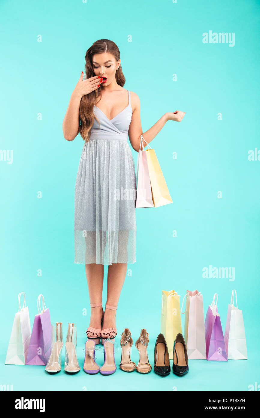 aecd661d0304 Full length photo of young shopaholic woman 20s in dress shopping and  doubting while looking at