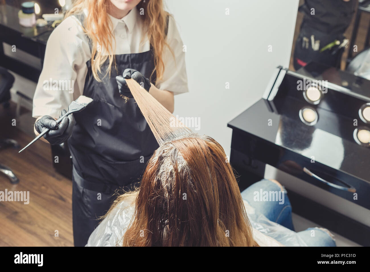 Female stylist applying a dye to the clients hair at beauty salon - Stock Image