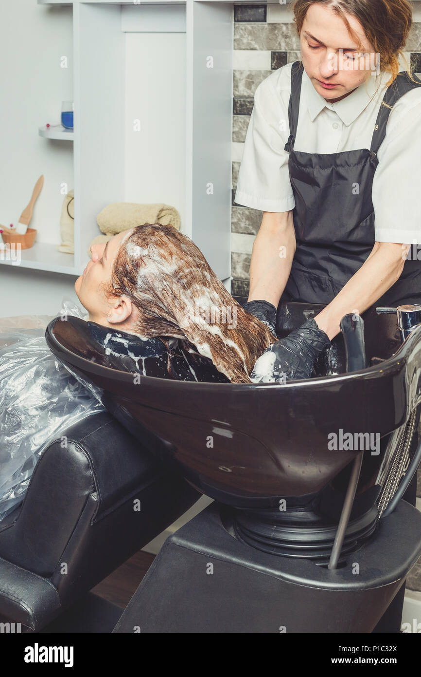 Hair wash procedure in a beauty salon. A hair dresser is washing her clients head in professional sink - Stock Image