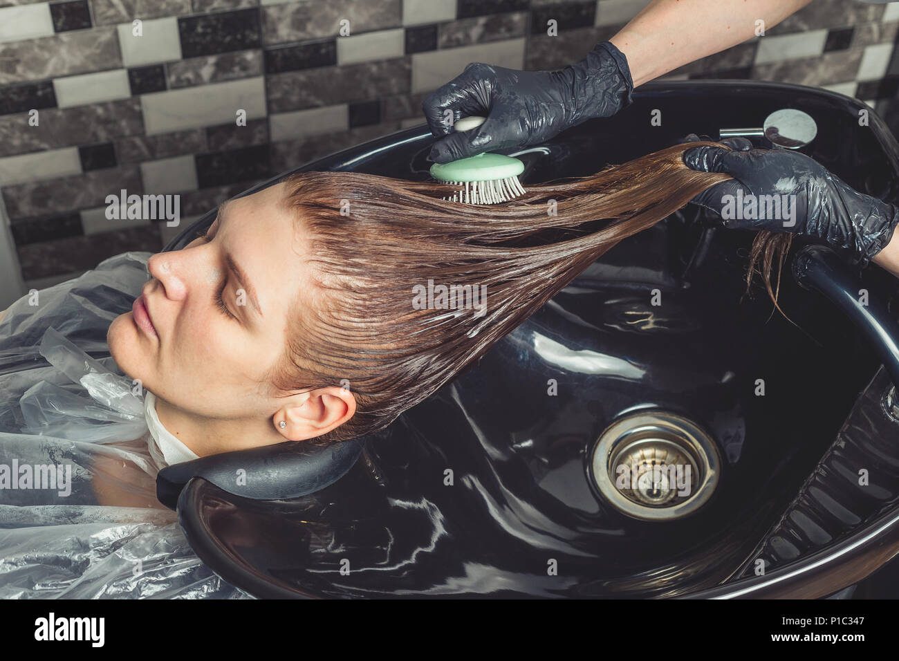 Haircare procedure in beauty salon. Hairdresser is brushing woman's hair spreading a treatment mask or conditioner - Stock Image