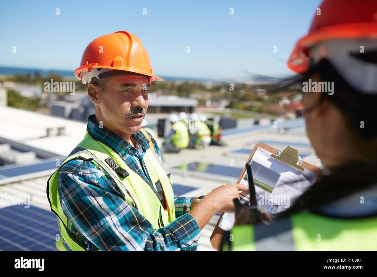 Engineers discussing paperwork at alternative energy power plant - Stock Image