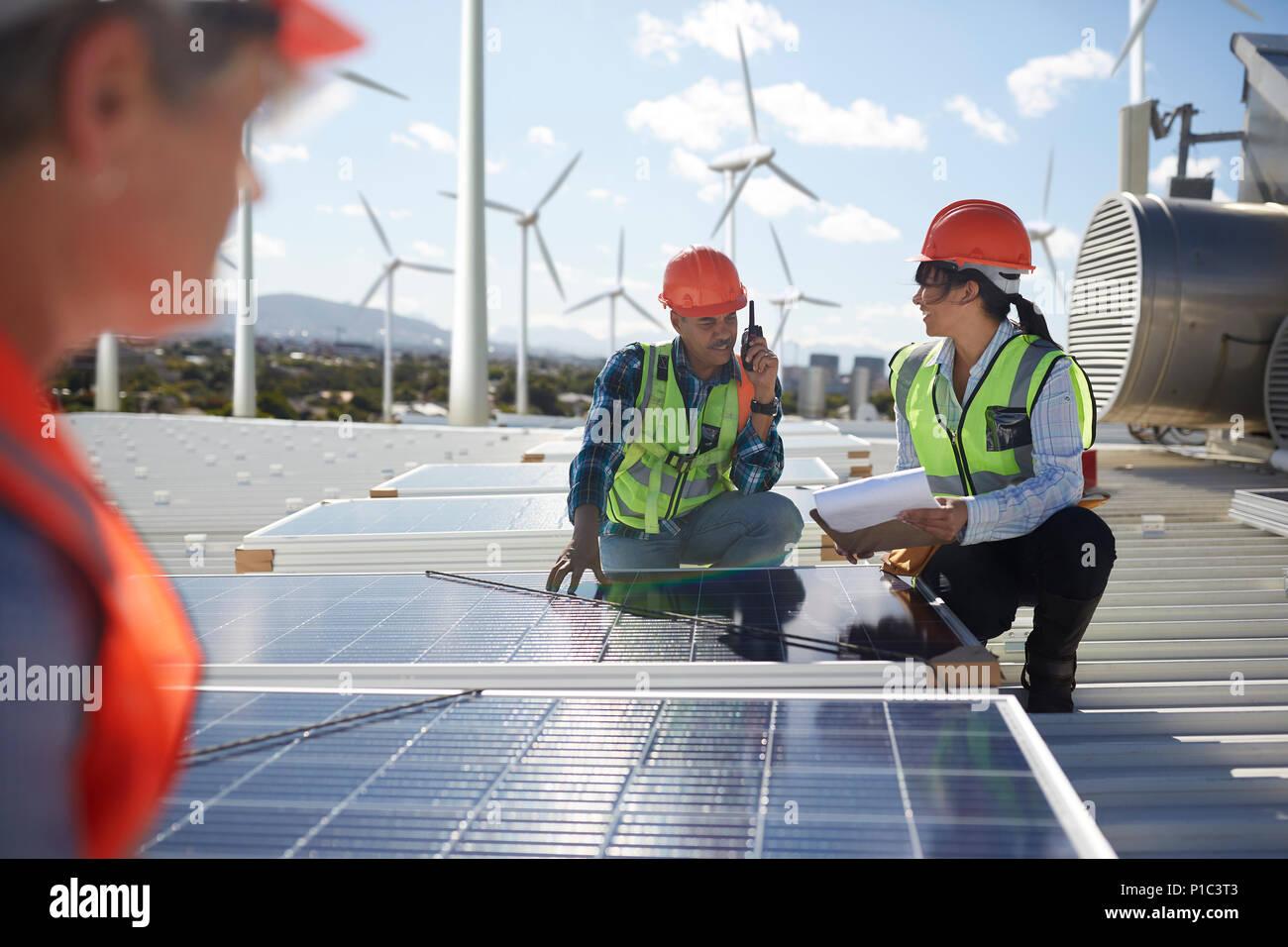 Engineers examining solar panels at alternative energy power plant - Stock Image