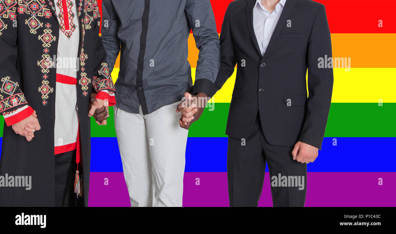 Men of different nationalities hold hands against the background of the LGBT flag. The concept of freedom and human rights - Stock Image