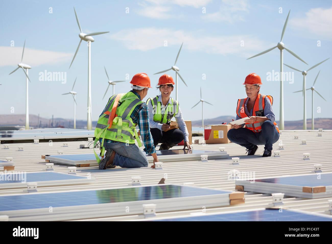 Engineers installing solar panels at alternative energy power plant - Stock Image