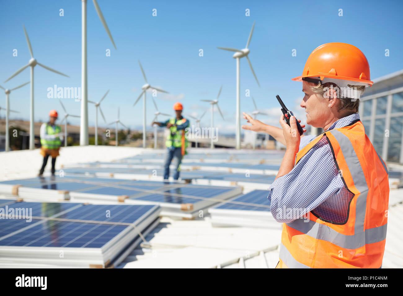 Female engineer using walkie-talkie at alternative energy power plant - Stock Image