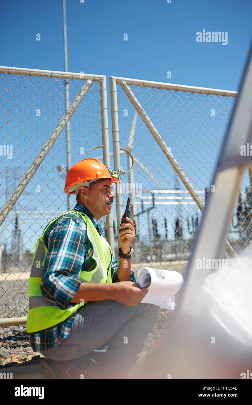 Engineer with walkie-talkie at sunny power plant - Stock Image