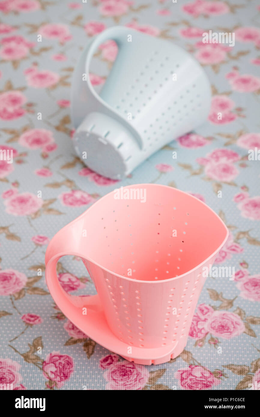 Colorful plastic colanders with handles on blue and pink floral pattern Stock Photo