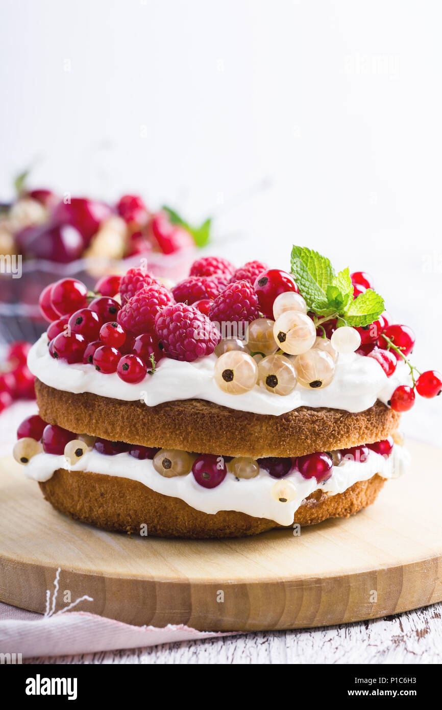 Cake with cream cheese and fresh berries on rustic wooden board - Stock Image