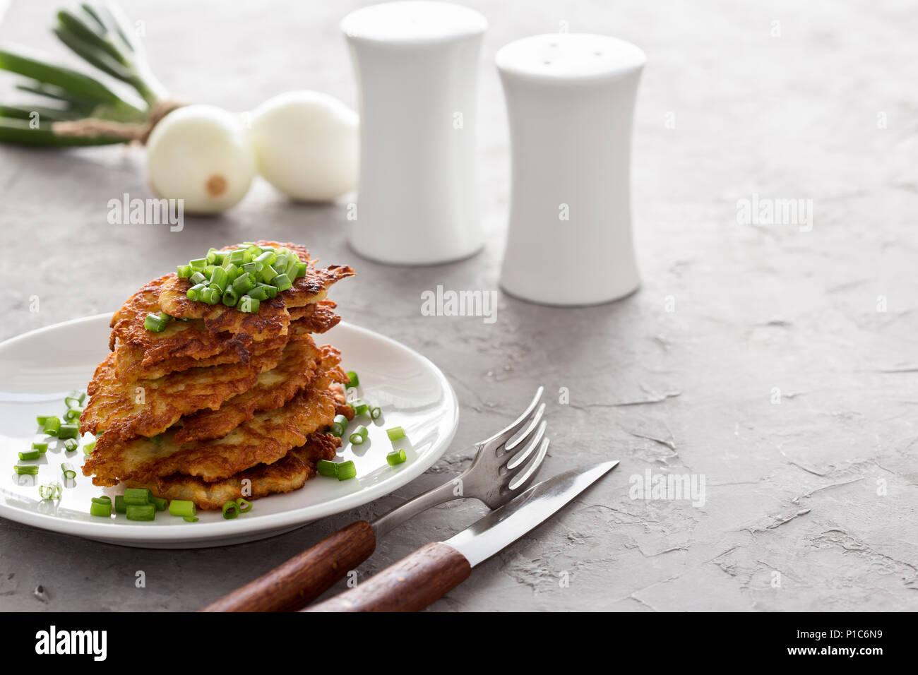 Classic Ukrainian dish deruny, potato pancakes on white plate - Stock Image
