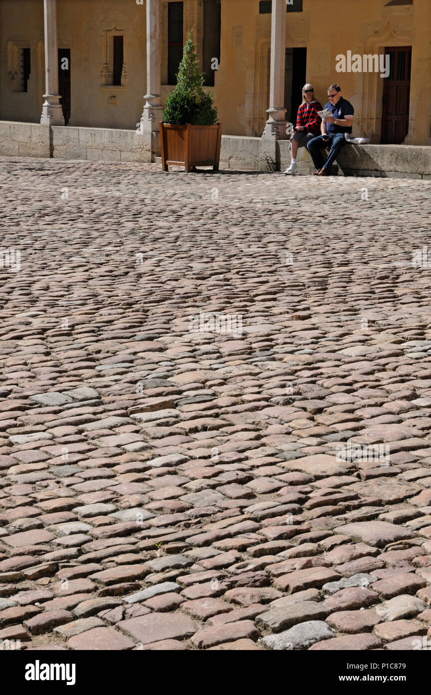 Seated couple reading brochure in front of stone sets paving in courtyard of Hotel Dieu medieval hospital Beane France Stock Photo