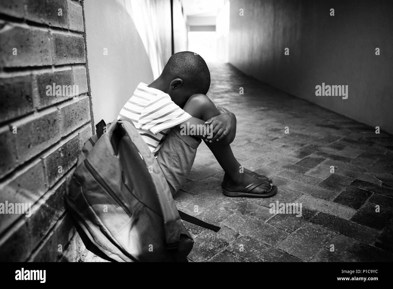 Boy sitting alone on school corridor stock image
