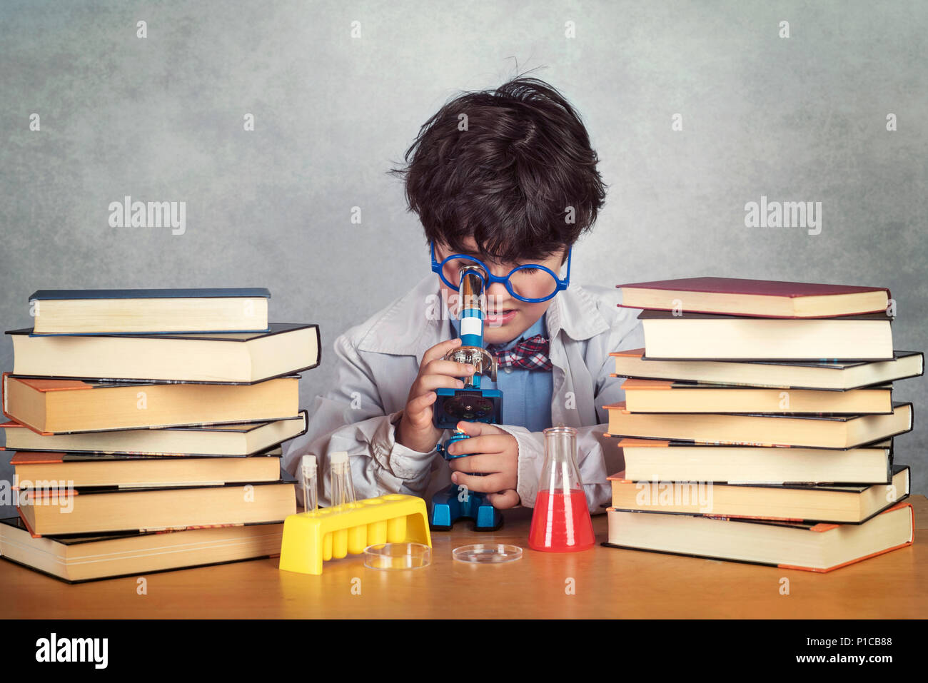 boy is making science experiments on gray background - Stock Image