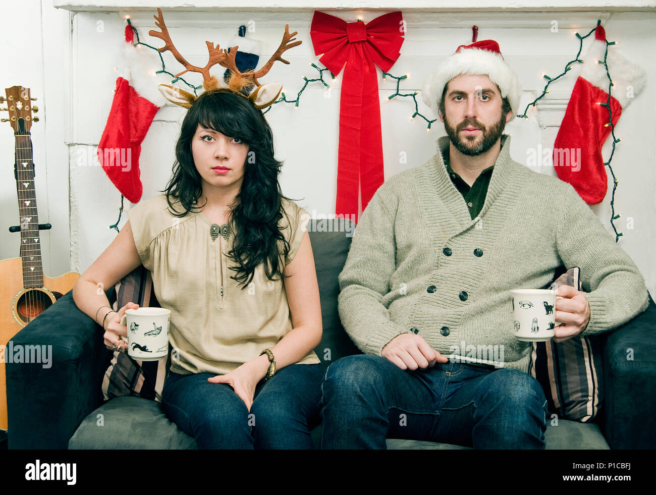 A couple (20's-30's) (twenties-thirties) holding mugs and sitting on a sofa posting for an ironic holiday portrait. - Stock Image