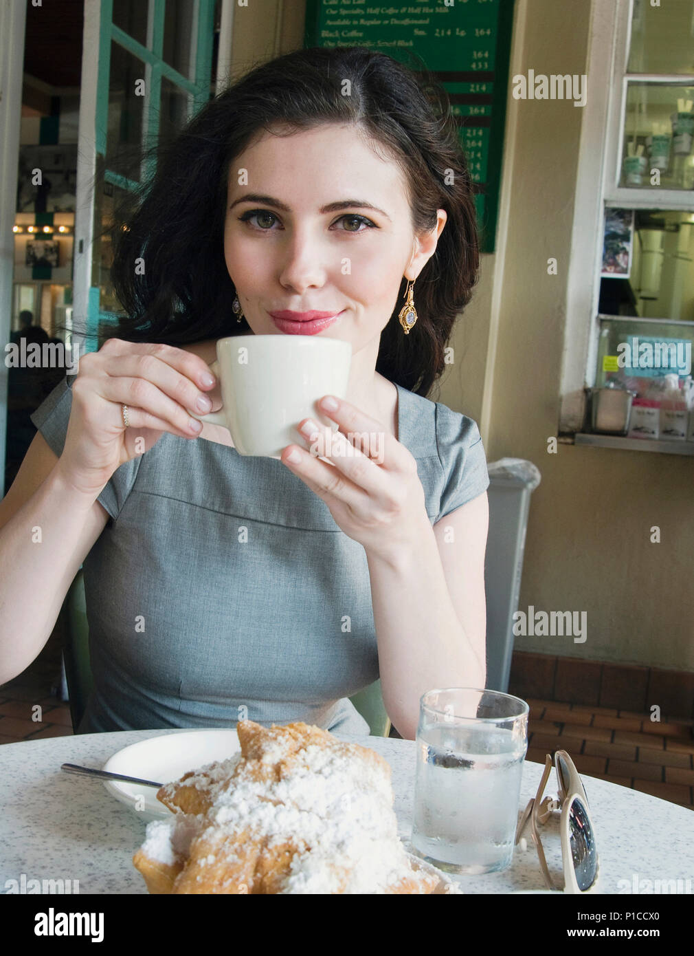 A woman eating a beignet and drinking coffee at Cafe du Monde in New Orleans, Louisiana - Stock Image