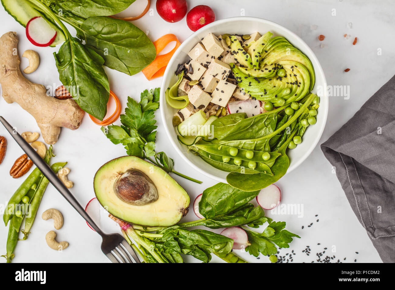 Healthy food flat lay. Buddha bowl with tofu, rice, avocado and vegetables. Healthy vegan food concept. - Stock Image