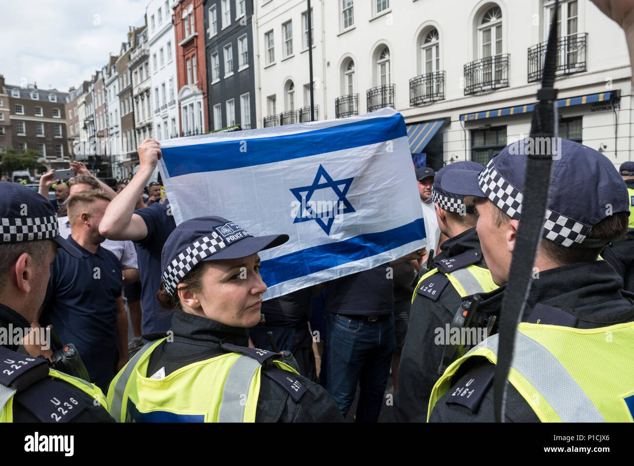 Opposition protesters hold an Israeli flag during the Al Quds Day rally.  The Al Quds Day rally is an event which is supposed to highlight the plight of the Palestinian people and raise awareness of Islamic persecution around the world. The rally has caused controversy across the UK because speakers at the event openly call for the destruction of Israel and some participants wave the flag of Hezbollah, a proscribed terrorist group. - Stock Image