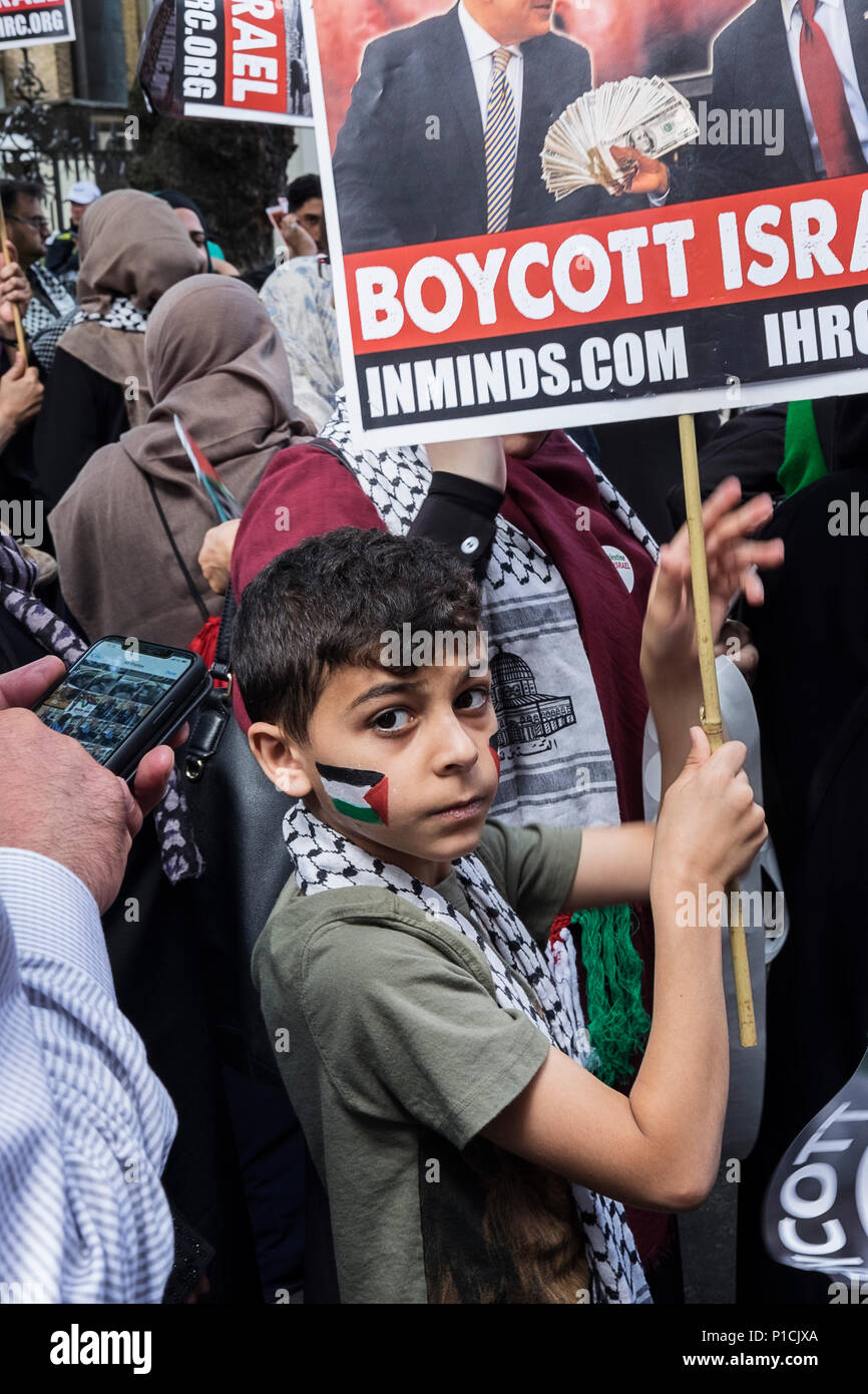 A child with the Palestinian flag painted on his cheek holds a sign calling for people to boycott Israel. Al Quds Day rally.  The Al Quds Day rally is an event which is supposed to highlight the plight of the Palestinian people and raise awareness of Islamic persecution around the world. The rally has caused controversy across the UK because speakers at the event openly call for the destruction of Israel and some participants wave the flag of Hezbollah, a proscribed terrorist group. - Stock Image