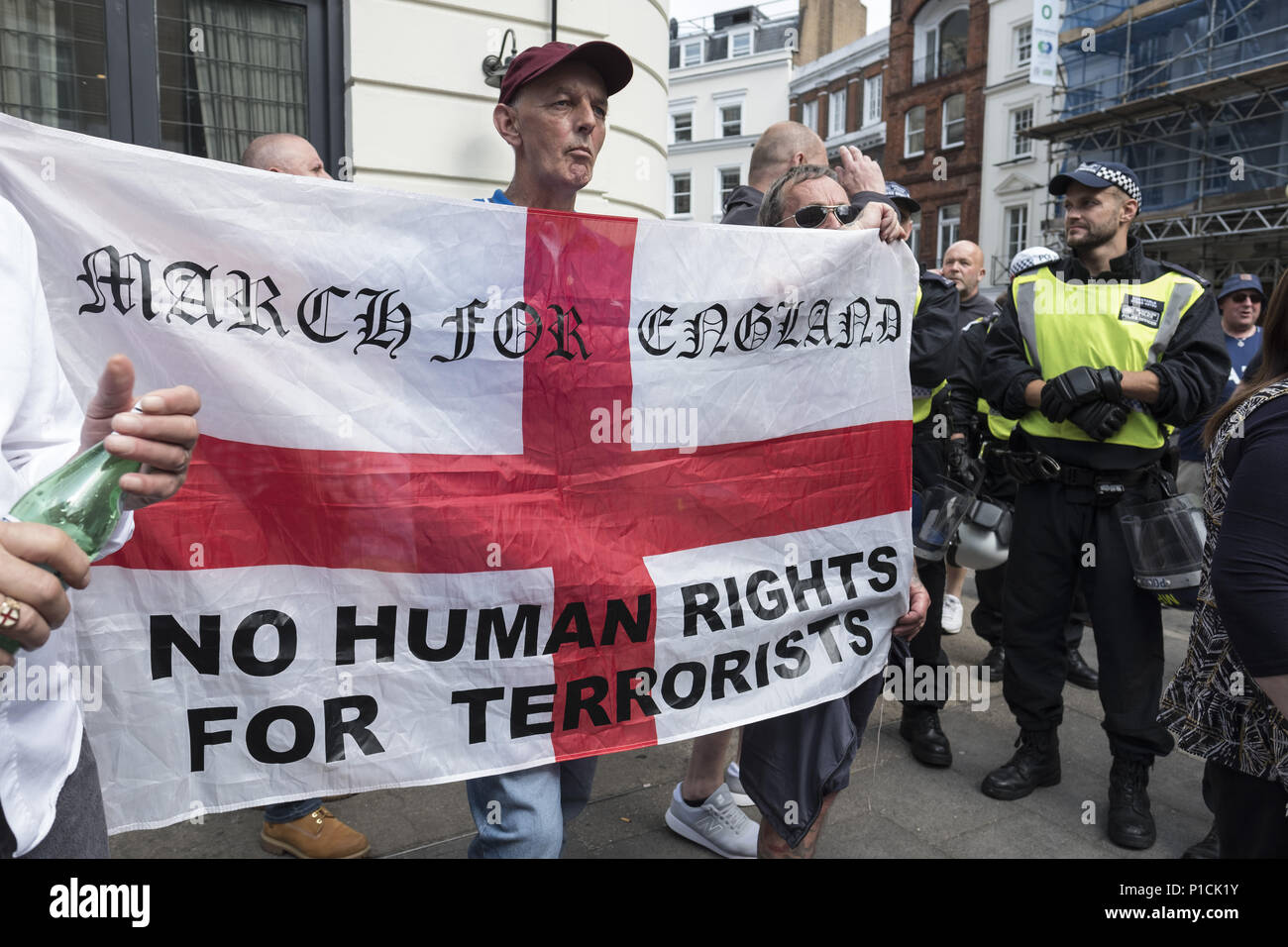 London, UK. 10th June, 2018. A counter protester holds an English flag in opposition to the Al Quds Day rally.The Al Quds Day rally is an event which is supposed to highlight the plight of the Palestinian people and raise awareness of Islamic persecution around the world. The rally has caused controversy across the UK because speakers at the event openly call for the destruction of Israel and some participants wave the flag of Hezbollah, a proscribed terrorist group. Credit: Edward Crawford/SOPA Images/ZUMA Wire/Alamy Live News - Stock Image