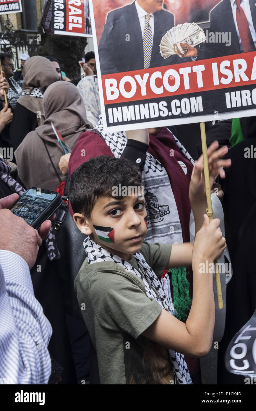 London, UK. 10th June, 2018. A child with the Palestinian flag painted on his cheek holds a sign calling for people to boycott Israel. Al Quds Day rally.The Al Quds Day rally is an event which is supposed to highlight the plight of the Palestinian people and raise awareness of Islamic persecution around the world. The rally has caused controversy across the UK because speakers at the event openly call for the destruction of Israel and some participants wave the flag of Hezbollah, a proscribed terrorist group. Credit: Edward Crawford/SOPA Images/ZUMA Wire/Alamy Live News - Stock Image